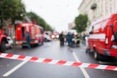 障碍磁带红色和空白线路在消防队员和消防车背景的在工作 红色白色警告磁带 库存图片