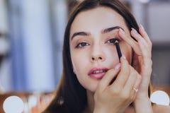 难以相信地使用黑眼线膏的美丽的妇女 免版税库存照片
