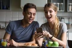 难以相信的好消息惊奇的激动的夫妇看sm 免版税库存图片