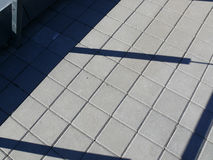 难倒在栏杆的屋顶与方形的瓦片和阴影 免版税库存图片