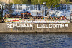 难民在柏林欢迎街道画和难民小船 免版税库存图片