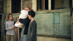 难民孩子和他们的母亲有一个孩子的胳膊的在被轰炸的房子背景  战争,地震,火 影视素材