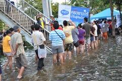 难民排队拾起在曼谷,泰国一条被充斥的街道的免费食物, 2011年10月31日 免版税图库摄影