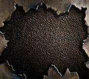 难看的东西与被撕毁的边缘的金属背景 免版税库存照片