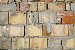 难看的东西变老了在好光的被风化的破裂的砖墙表面纹理 免版税库存照片