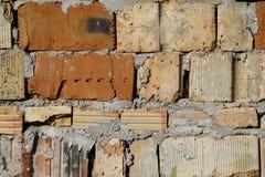难看的东西变老了在好光的被风化的破裂的砖墙表面纹理 免版税库存图片