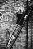 难看的东西时尚:在方格的裙子和夹克的逗人喜爱的女孩不拘形式的模型坐梯子 黑色白色 库存图片
