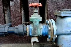 难看的东西生锈的工业自来水管子和阀门 免版税库存照片