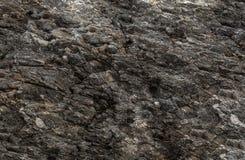 难看的东西背景纹理老石墙坑洼风化了,一座黑暗的山的自然表面部分 免版税图库摄影