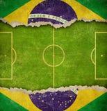 难看的东西足球或巴西背景橄榄球场和旗子  库存图片