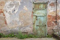 难看的东西金属门,破裂的红砖墙壁 免版税库存照片