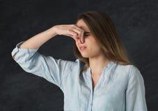 难闻的气味情况 少妇捏她的鼻子 图库摄影