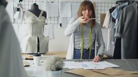 雄心勃勃的创造性的女性裁缝在演播室书桌安置服装剪影并且射击他们与智能手机 影视素材