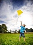 雄心勃勃的男孩飞行风筝 库存照片