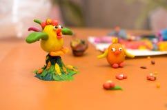 雄鸡和鸡从彩色塑泥在黄色背景 库存图片