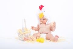 雄鸡服装的婴孩坐在一把疏散干草用力嚼秸杆的, 库存图片