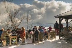 雅典,希腊2016年1月02日 在Mpafi避难所风雨棚的人放松的饮用的咖啡在帕尼萨山山在希腊 图库摄影
