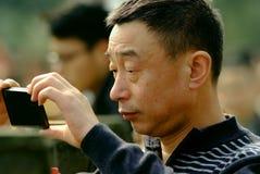 雅安中国人将集中使用一个手机拍摄。 免版税库存照片