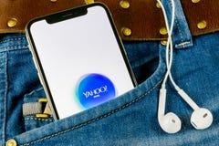 雅虎邮件在苹果计算机iPhone x智能手机屏幕特写镜头的应用象在牛仔裤装在口袋里 雅虎邮件app象 3d网络照片回报了社交 soc. 库存照片