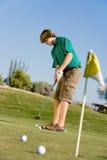 集中做的高尔夫球运动员轻轻一击 库存照片