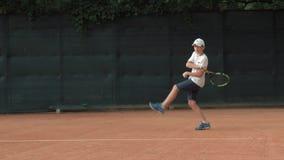 集中和集中于比赛和球拍命中球的雄心勃勃的网球员少年男孩在红色法院 股票录像