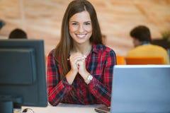 集中在工作 使用她的膝上型计算机的年轻美丽的妇女,当坐在椅子在她的工作地点时 免版税库存图片