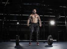 集中在杠铃锻炼前的肌肉赤裸上身的人 免版税库存照片