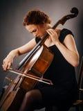 集中她使用的大提琴球员 免版税库存照片