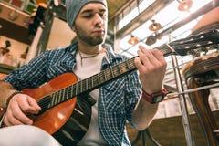 集中正确的技术的严肃的男性吉他弹奏者 免版税库存照片