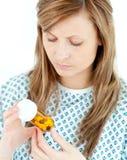 集中的女性看起来耐心的药片的她 库存图片