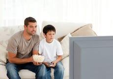 集中的父亲儿子电视注意 图库摄影