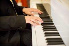 集中钢琴演奏家` s手于钢琴钥匙 乐队乐器 浪漫合理的起源 免版税库存图片
