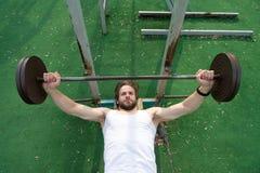 集中锻炼 人与杠铃的运动员训练 运动人增加重的杠铃 运动员强健的身体 免版税库存照片