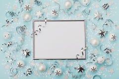 集会与五彩纸屑、球和星的狂欢节圣诞节背景装饰的银色框架在绿松石桌面视图 平的位置 库存图片