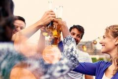 集会和享用在屋顶terrasse的不同种族的millenial小组朋友啤酒在日落 免版税图库摄影