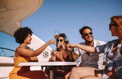 集会在有饮料的一条小船的朋友 免版税库存照片