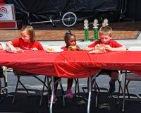 集市的孩子,参与西瓜吃contes的 图库摄影
