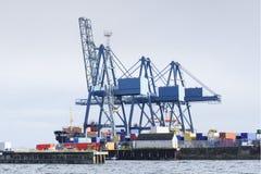 集装箱码头装载的和卸货的货物货物运输的起重机台架在码头围场沿海的格里诺克港口船坞 库存照片