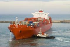 集装箱船和一条小猛拉小船 免版税库存图片