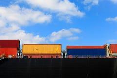 集装箱船和运输货柜的各种各样的品牌和颜色在一个举行的平台堆积的 免版税库存照片