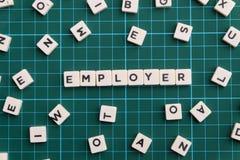 雇主词由方形的信件词制成在绿色方形的席子背景 图库摄影