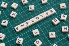 雇主词由方形的信件词制成在绿色方形的席子背景 免版税图库摄影