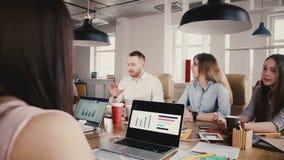 雇员与无法认出的上司谈话在桌上 办公室工作者与CEO在现代办公室会议上,摇摄射击4K谈话 股票视频