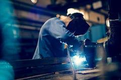 雇员与火花的焊接钢使用mig mag焊工 免版税图库摄影
