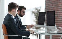 雇员与计算机一起使用在一个现代办公室 免版税库存图片