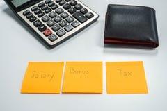 雇员在奖金以后的薪金管理和与计算器和钱包的税收减免 免版税库存图片