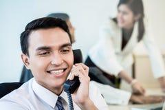 雇员在打企业电话的办公室 库存图片