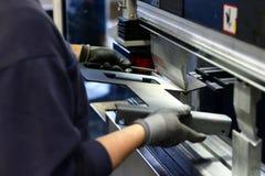 雇员在金属工艺公司中操作立弯机-弯曲进一步处理的金属板 库存照片