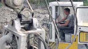 雇员处理一种挖掘机 培养杓子并且为工作做准备 股票录像