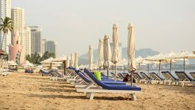 雇员延长阳伞 与许多假期的游人的芽庄市海滩 越南 Timelapse 免版税库存图片